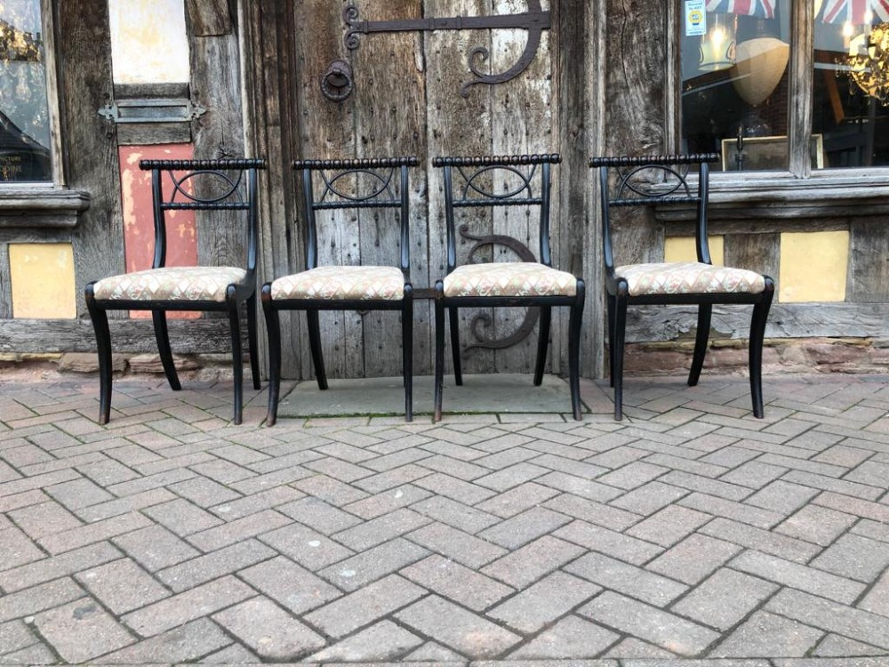 a set of four 19thc ebonised sabre leg chairs