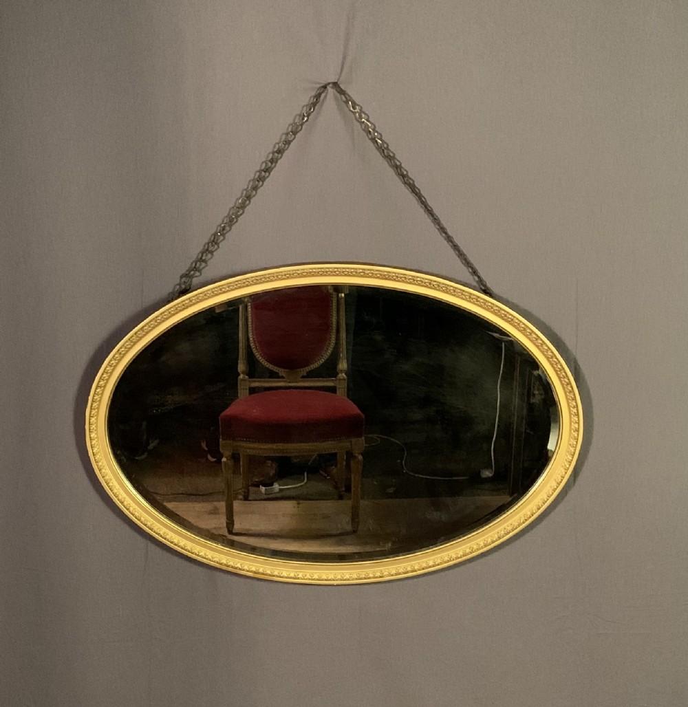 a large decorative edwardian oval gilt mirror