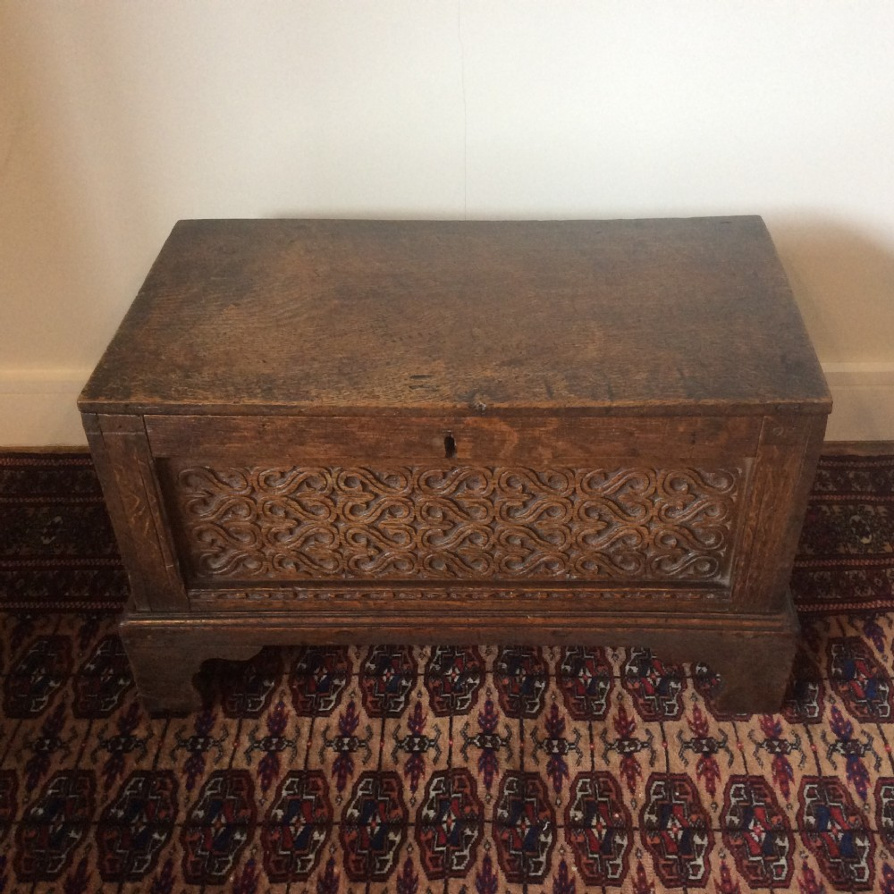 18th c small oak coffer down to four bracket shaped feet carved panels
