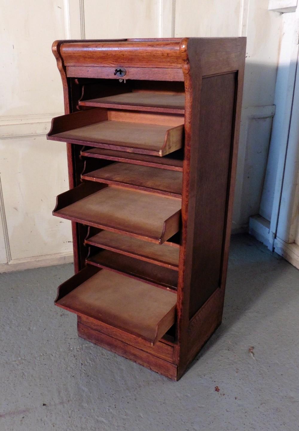 tambour fronted oak art deco filing cabinet with slide shelves