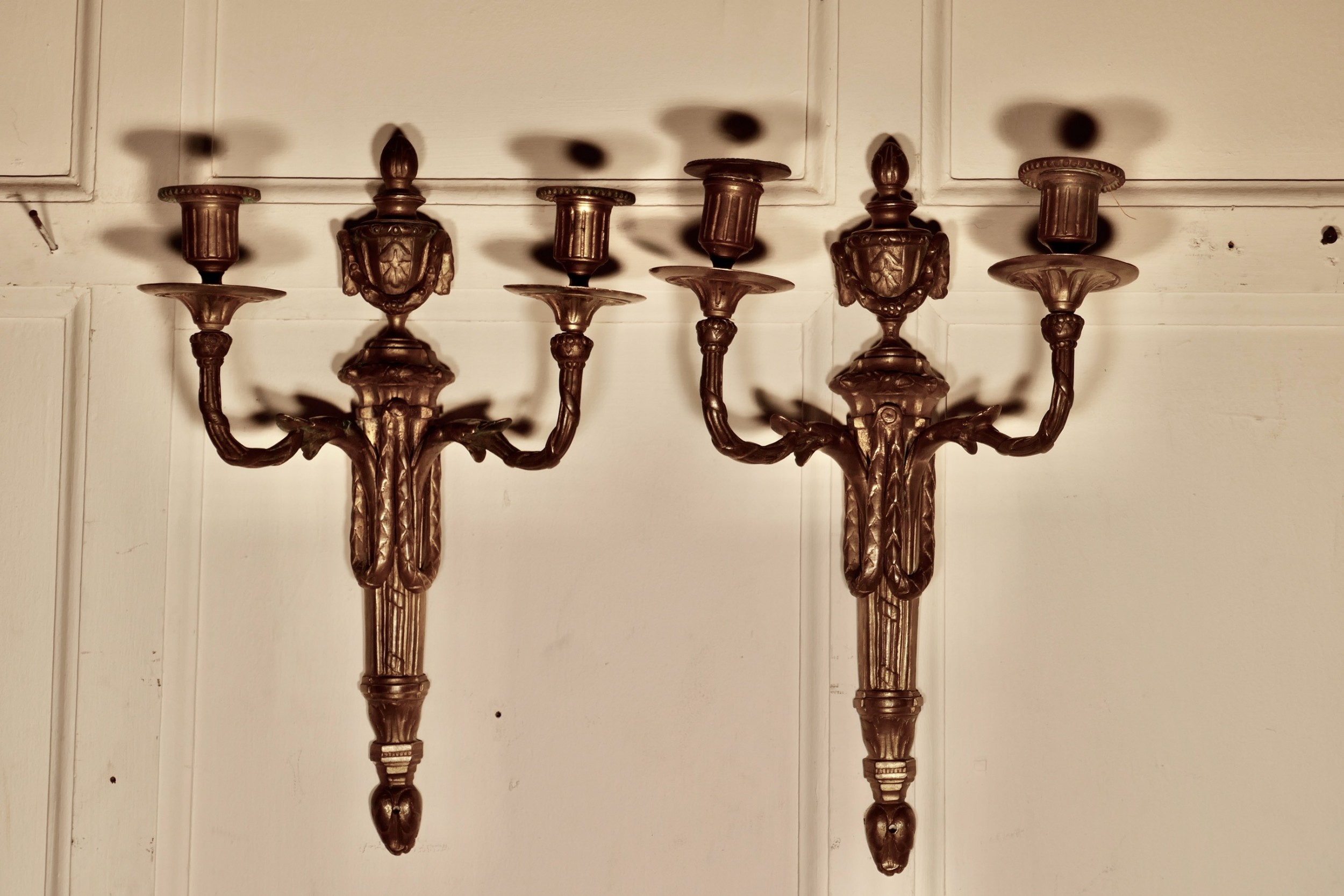 an early 19th century pair of french brass twin wall sconces