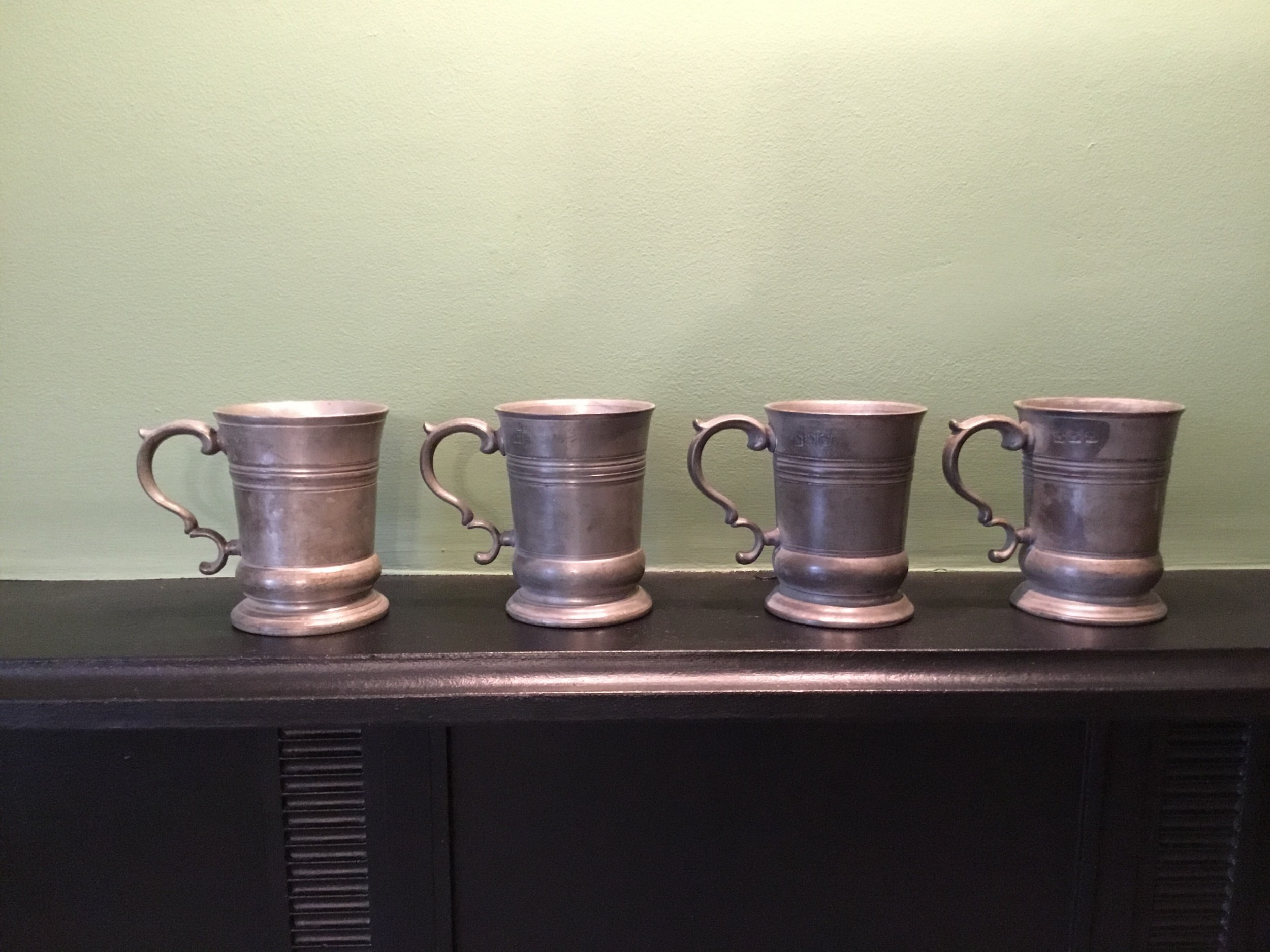 a set of four identical half pint pewter mugs