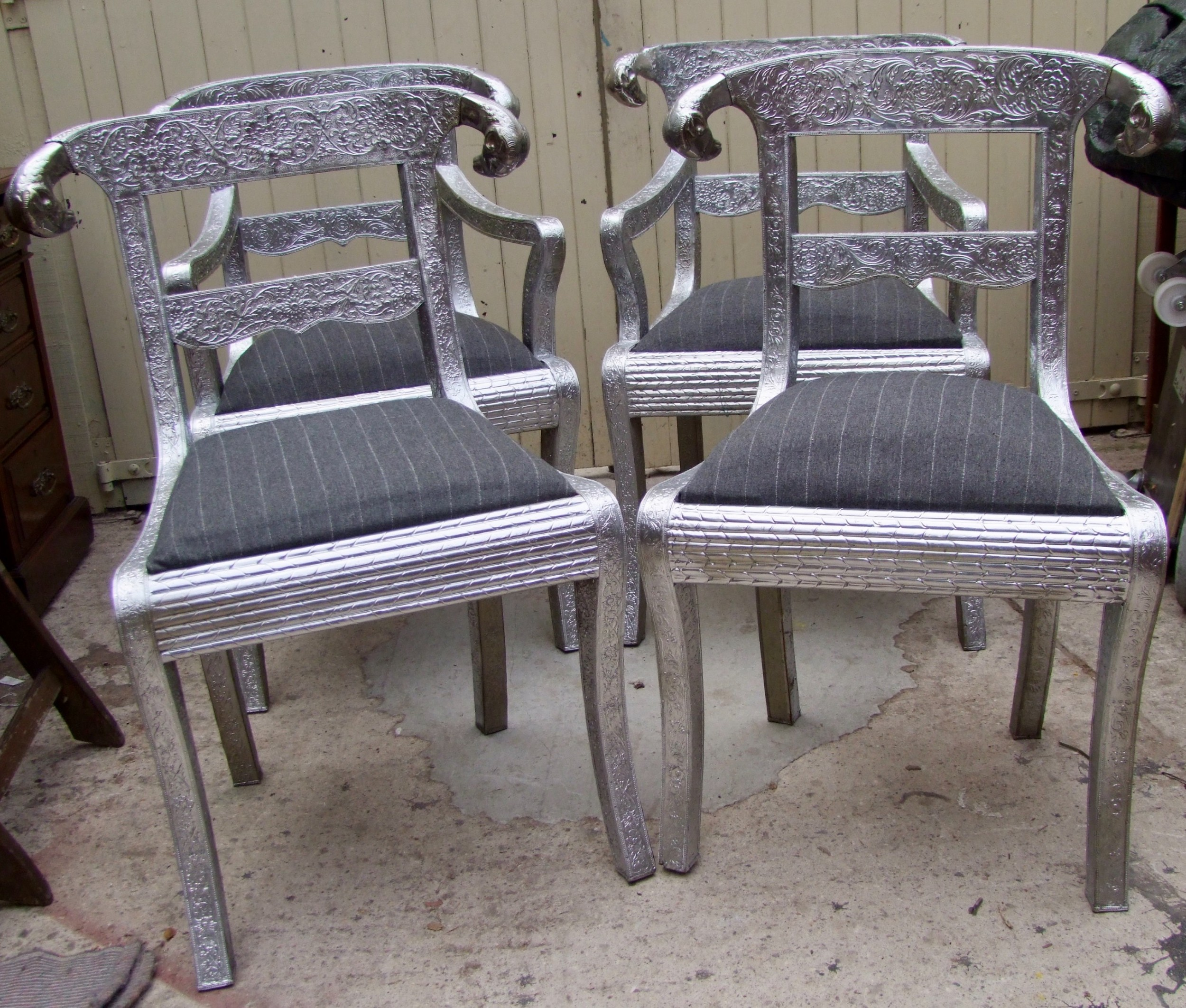 set of four two carvers and two singles unusual eastern hardwood chairs covered with silver embossed metal and with rams heads to the backs