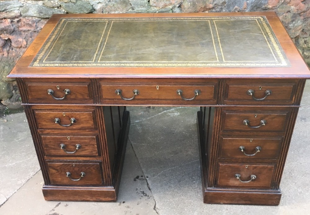 solid oak pedestal desk with green tooled leather insert
