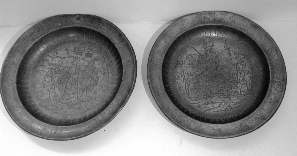 a pair of pewter engraved plates