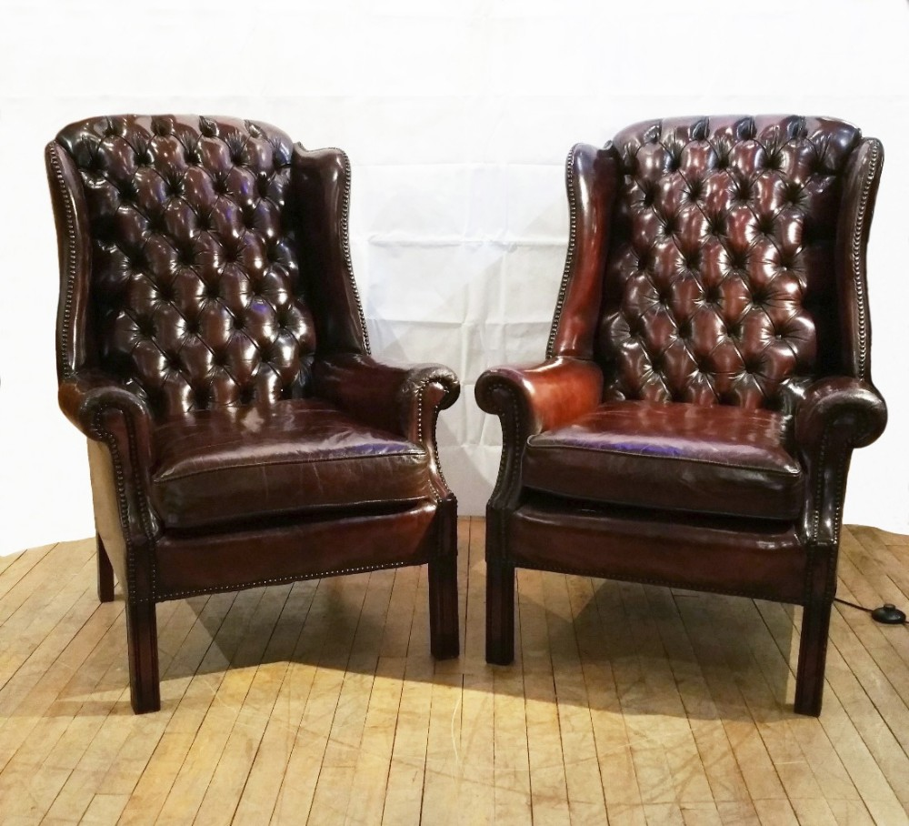 pair of deep buttoned leather upholstered edwardian wing chairs