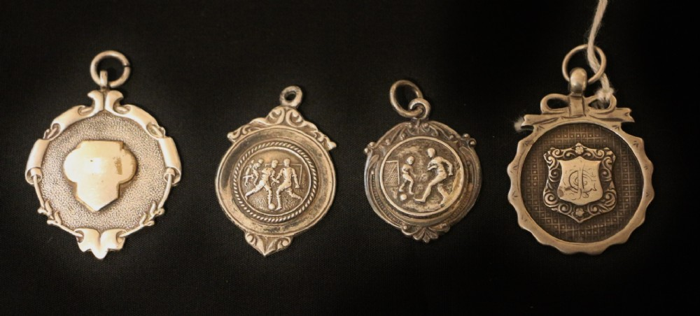 four early 20th century silver football medals