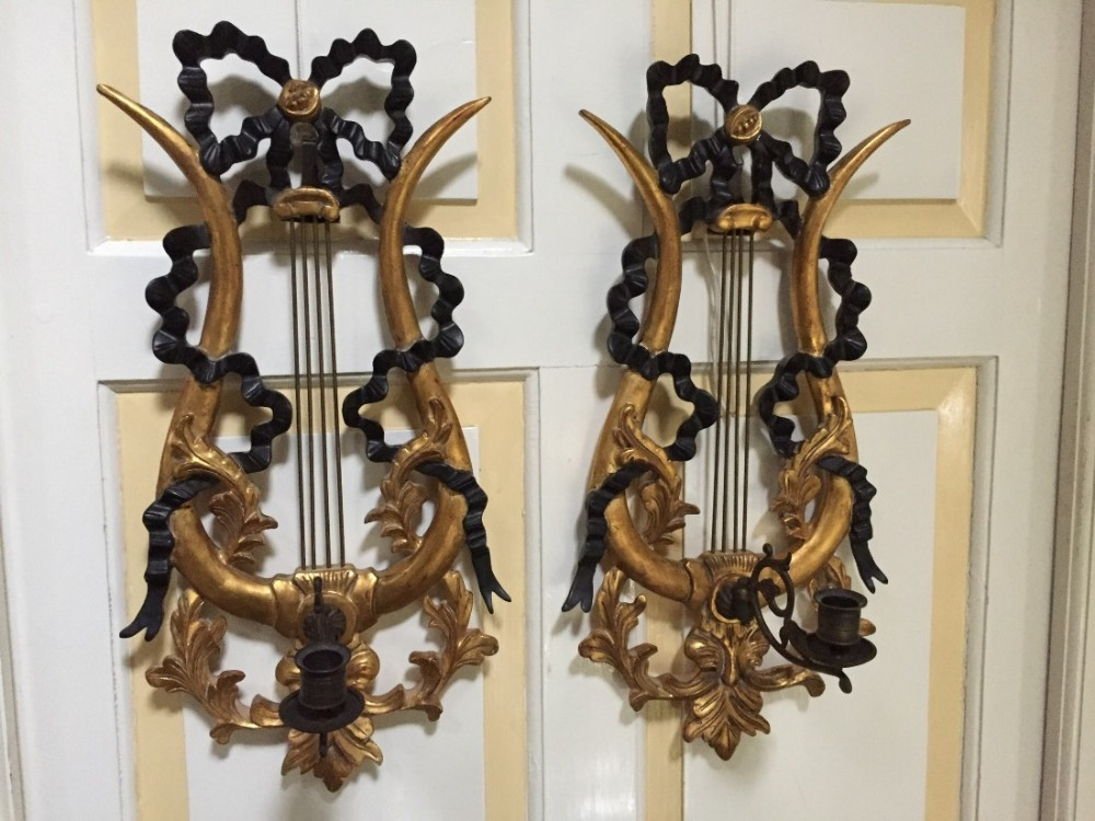 decorative pair of early c20th italian ebonised and gilt lyreform wall appliqus or girandoles with candlearms
