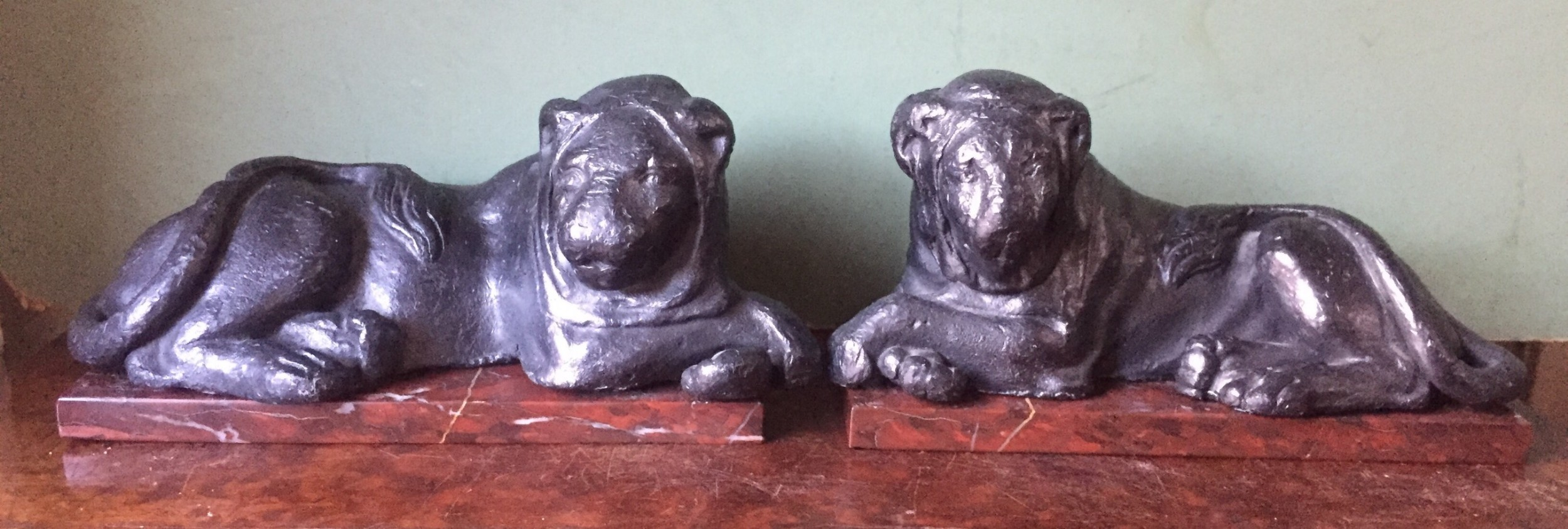 pair of early c19th 'grand tour' souvenir patinated castlead lions mounted upon rouge griotte marble plinth bases copies of the egyptian lions from the vatican rome
