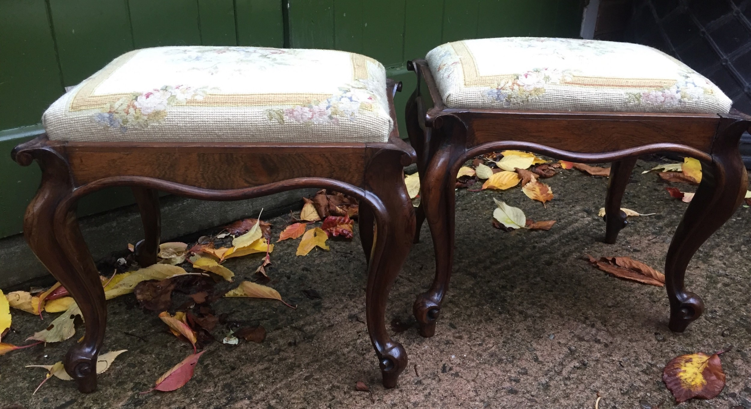 pair of mid c19th victorian period carved and figured rosewoodframed stools with needlework seats