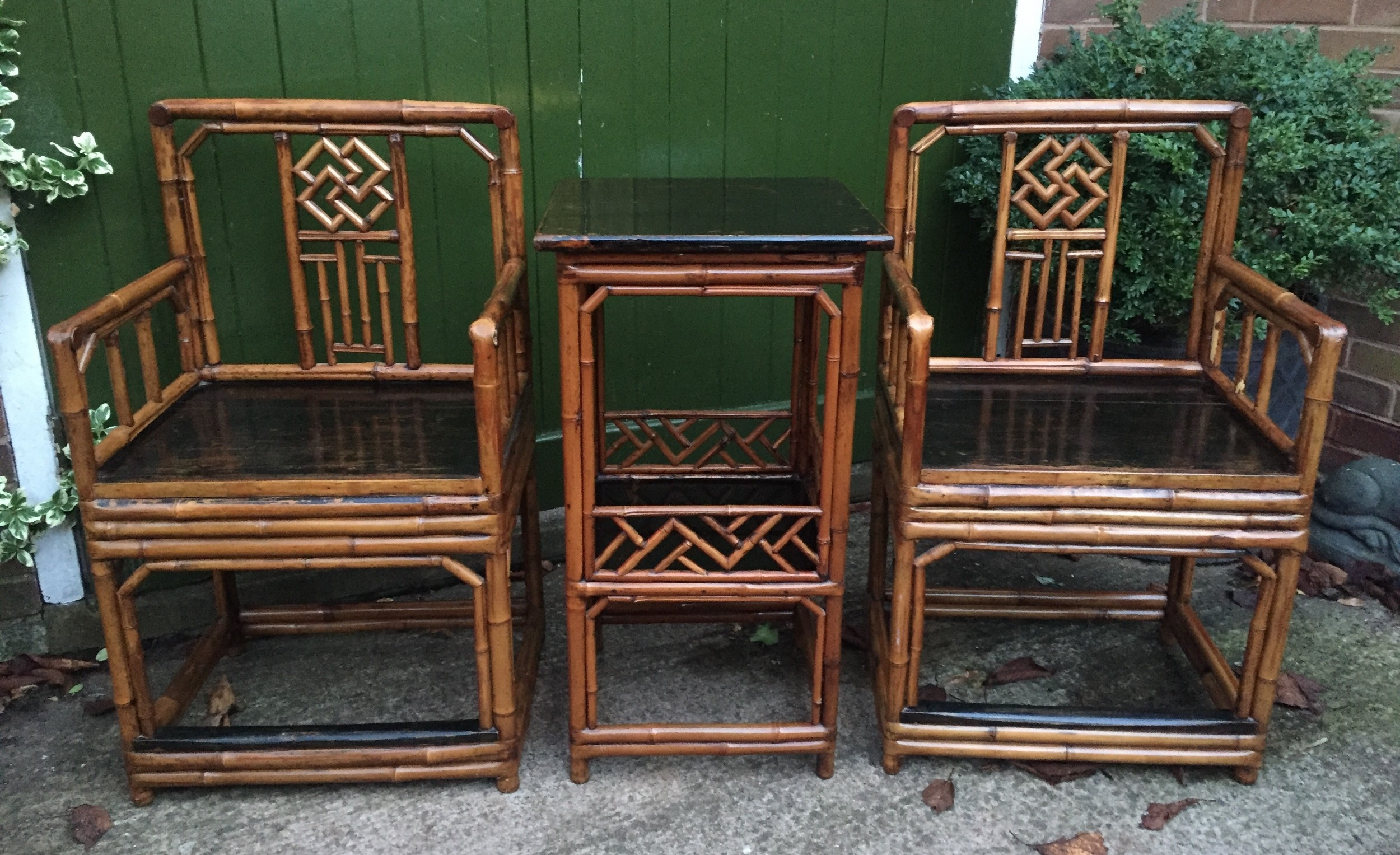 decorative pair of early c20th chinese polished bamboo and lacquer armchairs and table in the c18th manner