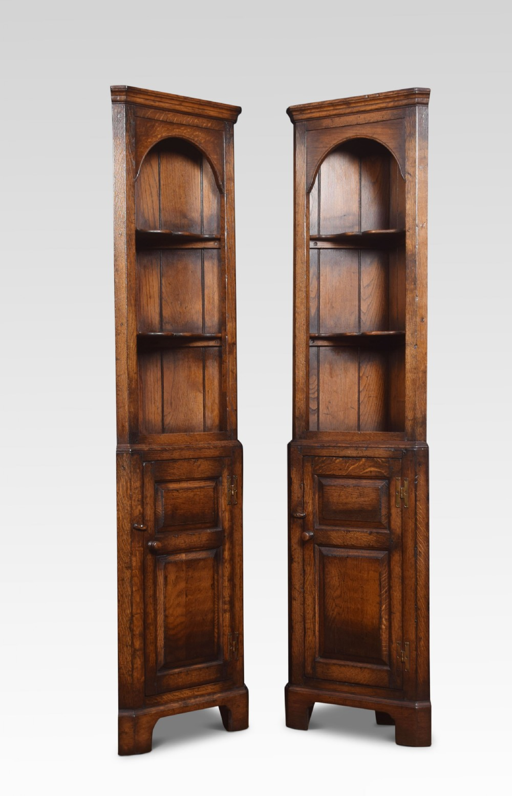pair of narrow oak floor standing corner cupboards