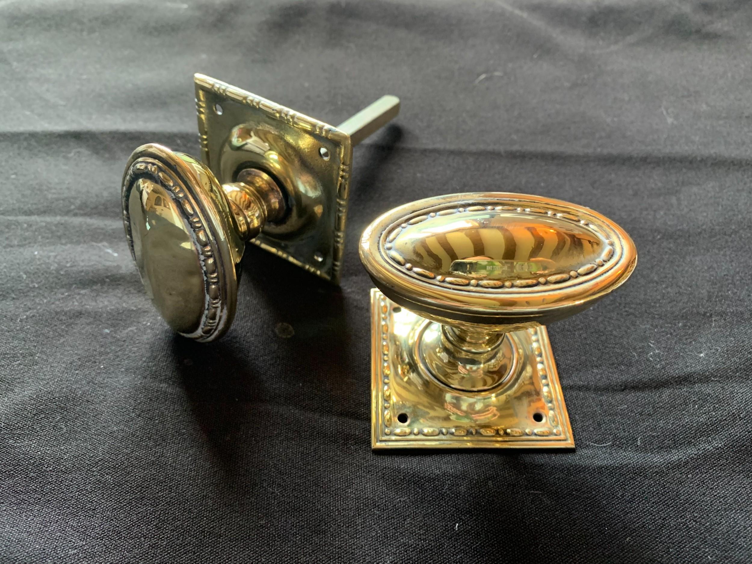 one pair of brass regency oval door knobs