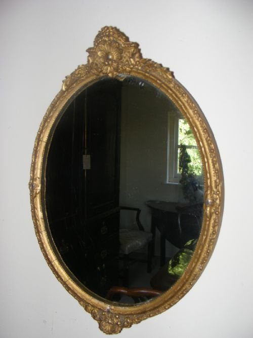 pair of small regency giltwood oval mirror with hand carved decoration c1820