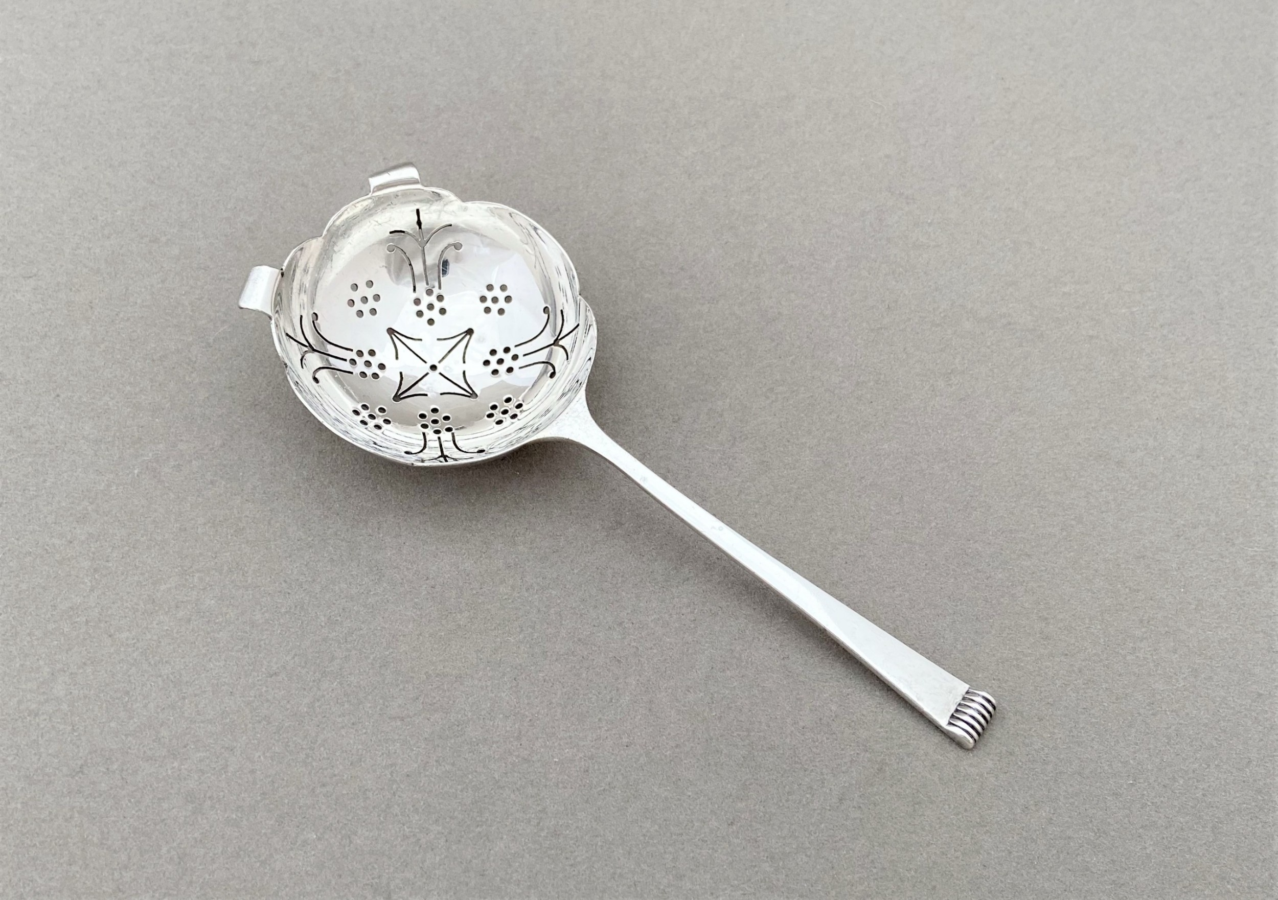 a lovely silver tea strainer in the art deco style