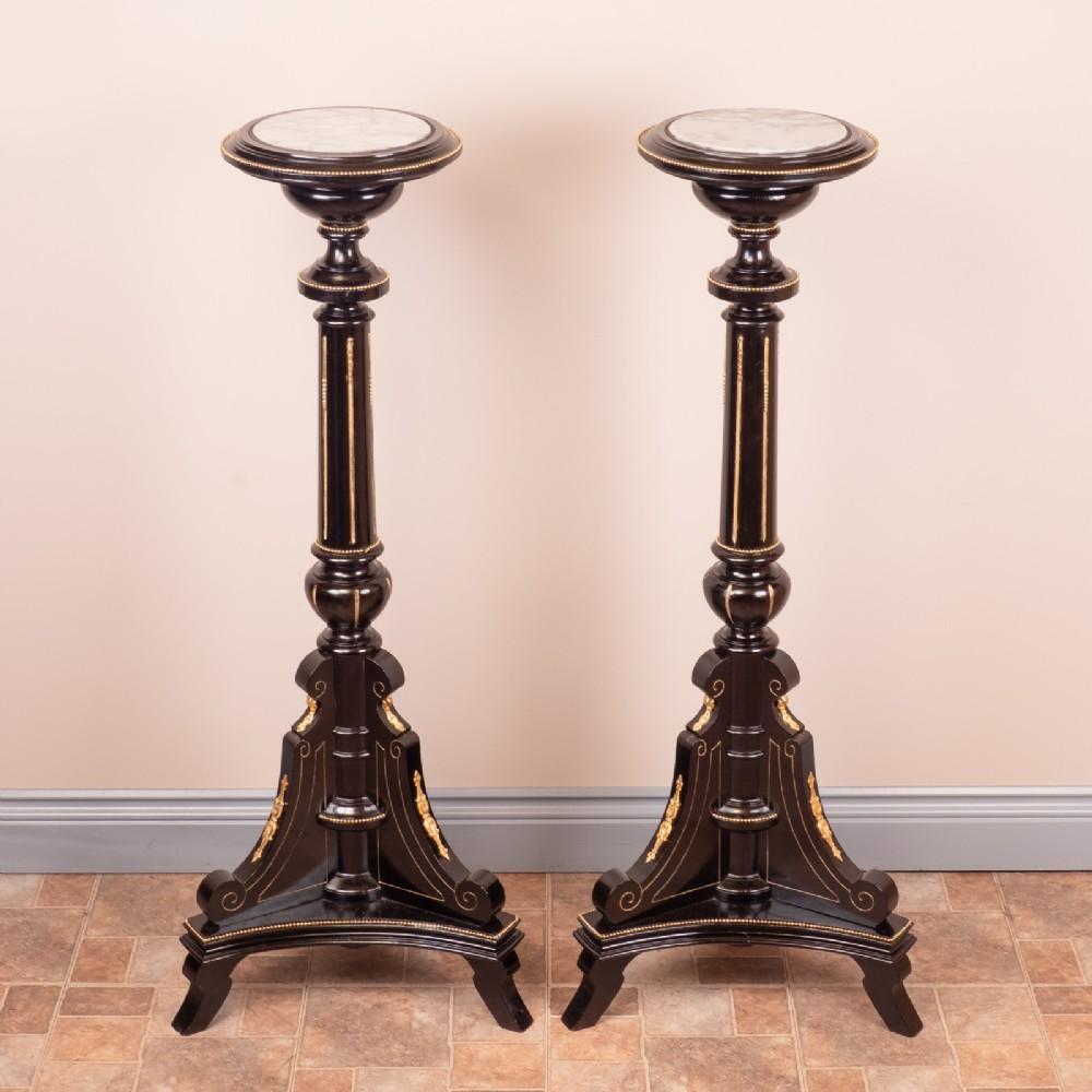 pair of ebonised highly decorative torcheres