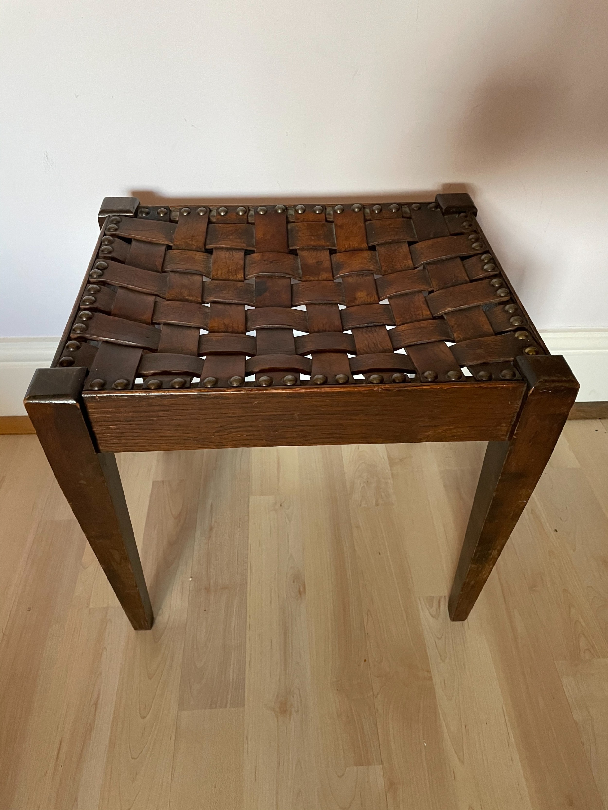 an arts and crafts oak and leather stool attributed to arthur simpson