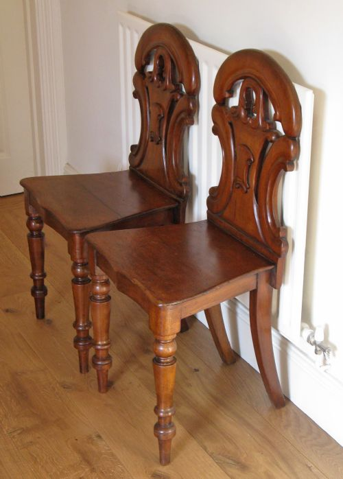 pair of victorian mahogany hall chairs with armorial carved fretcut backs