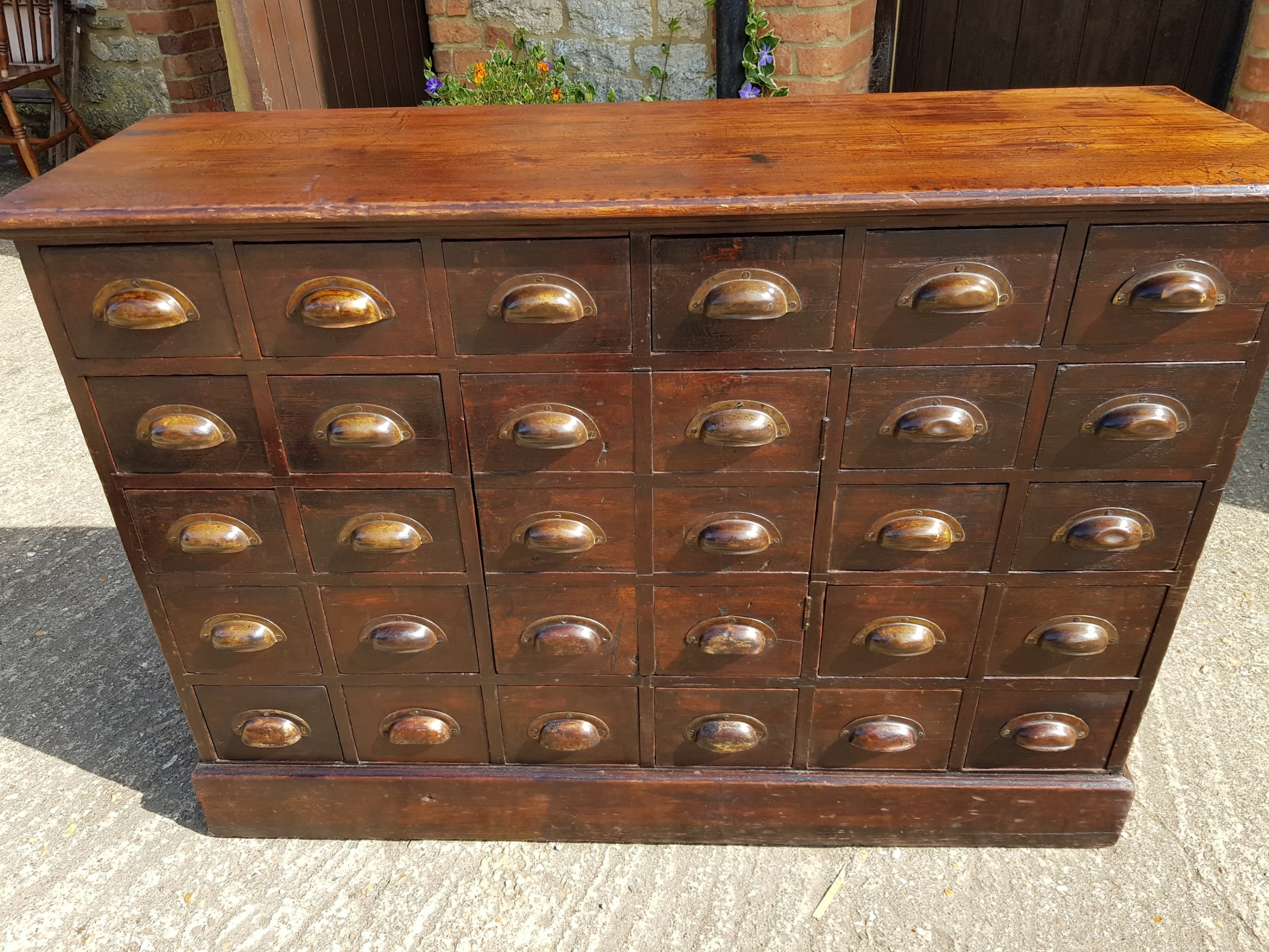 victorian pine bank of drawers with 24 drawers and a central cupboard door