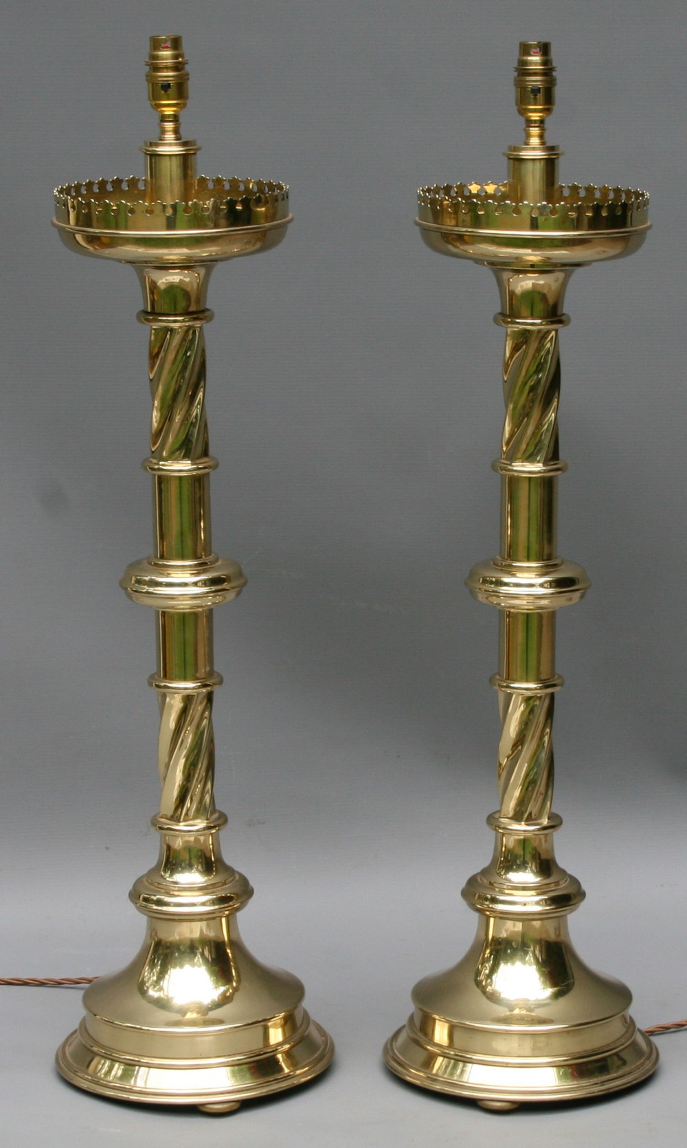 a large pair of victorian gothic brass candlesticks with crenelated rims
