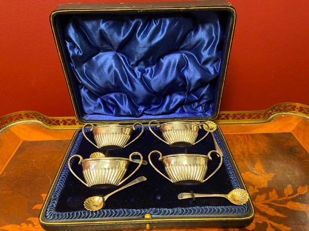 set of four boat shape silver salts with looped handles and four silver spoons
