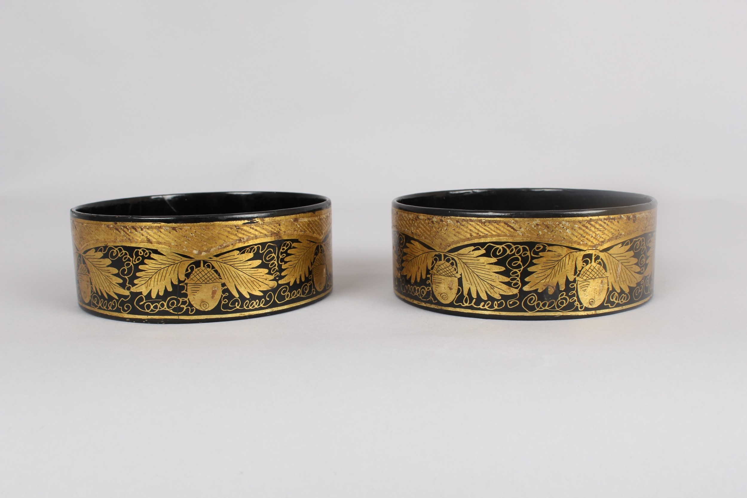 pair of regency black and gilt papiermache coasters