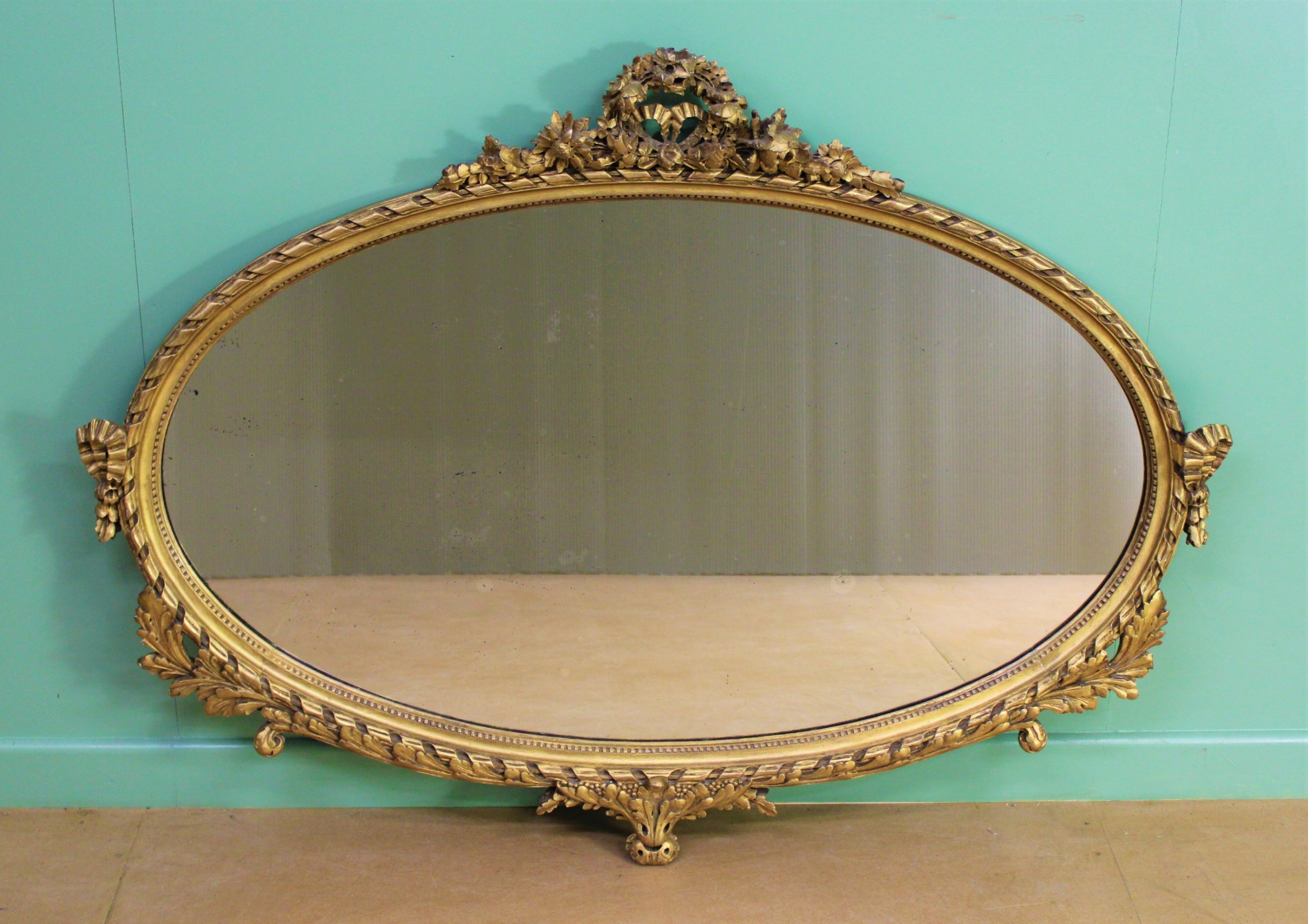 large oval neoclassical gilt wall mirror