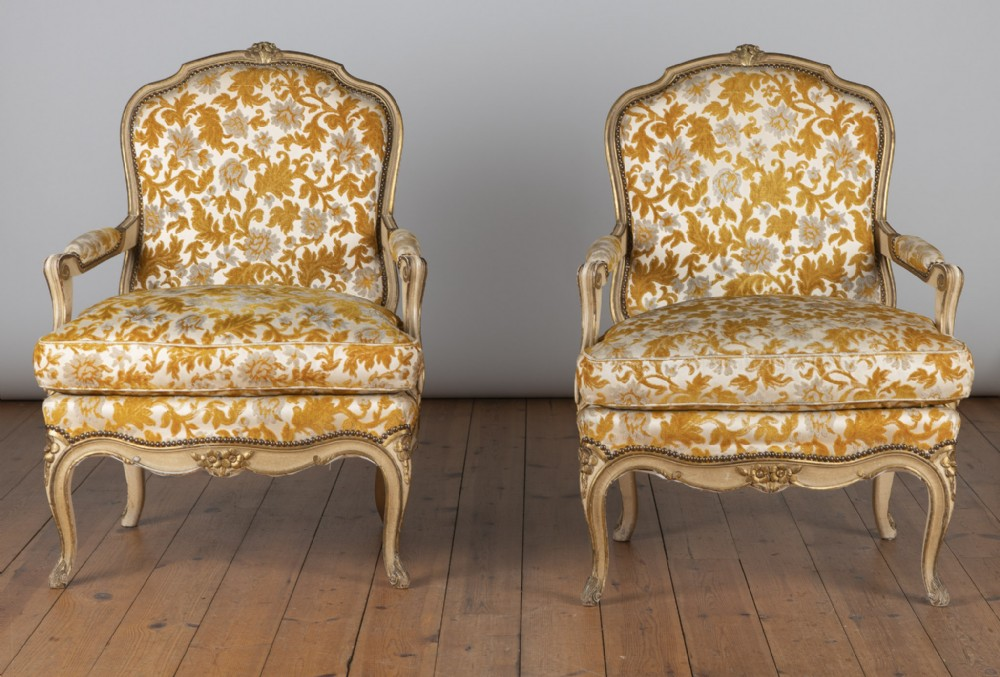 pair of large french louis xv style painted and gilt upholstered cabriolet armchairs