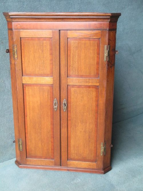 an oak and mahogany 2door hanging corner cupboard