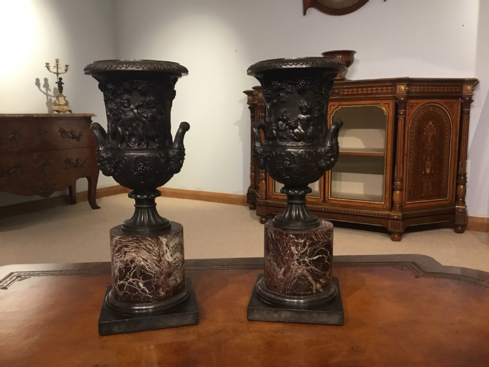 a pair of 19th century french bronze urns on circular marble bases