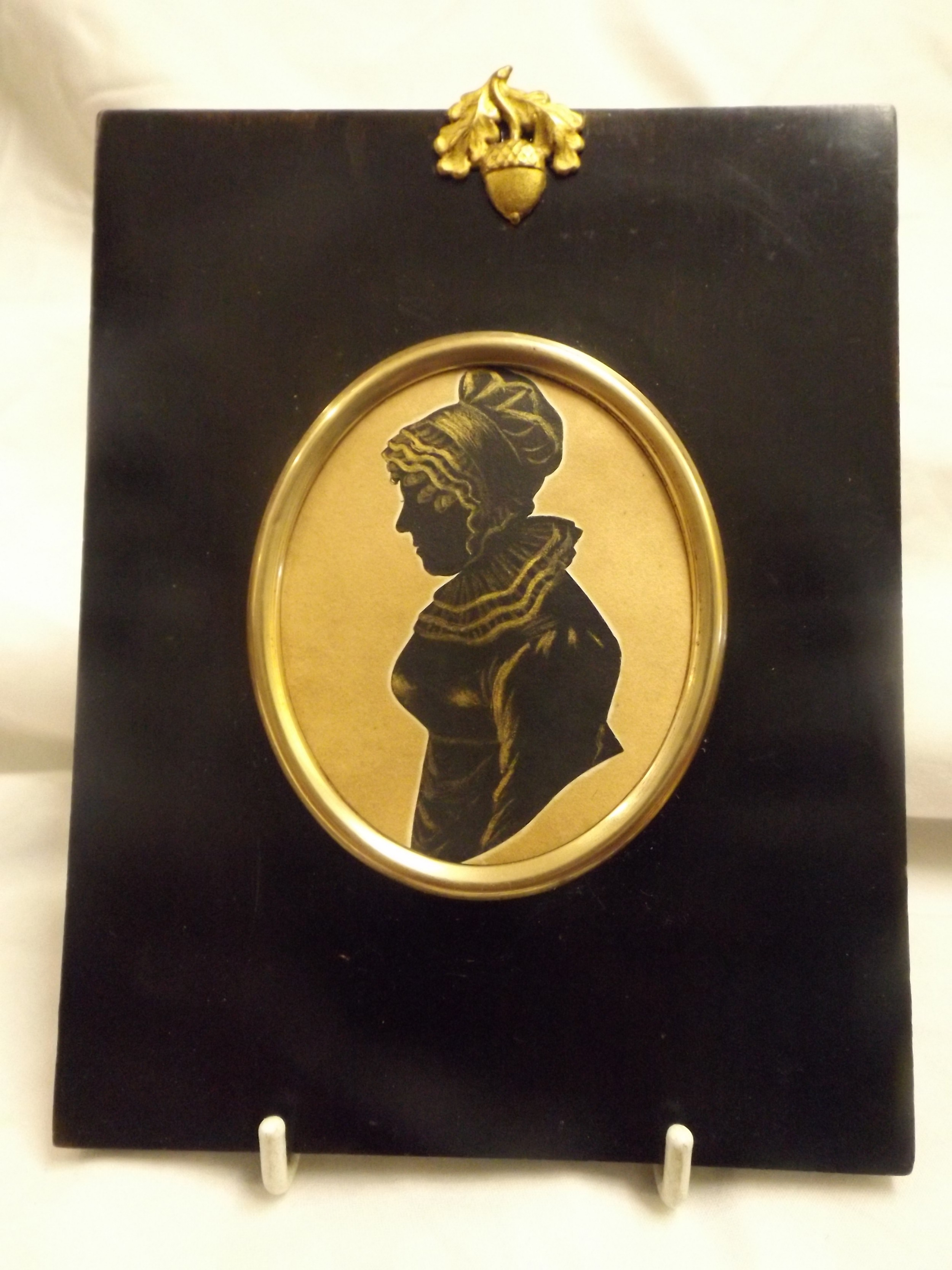 miniature silhouette of an old lady with gold highlights