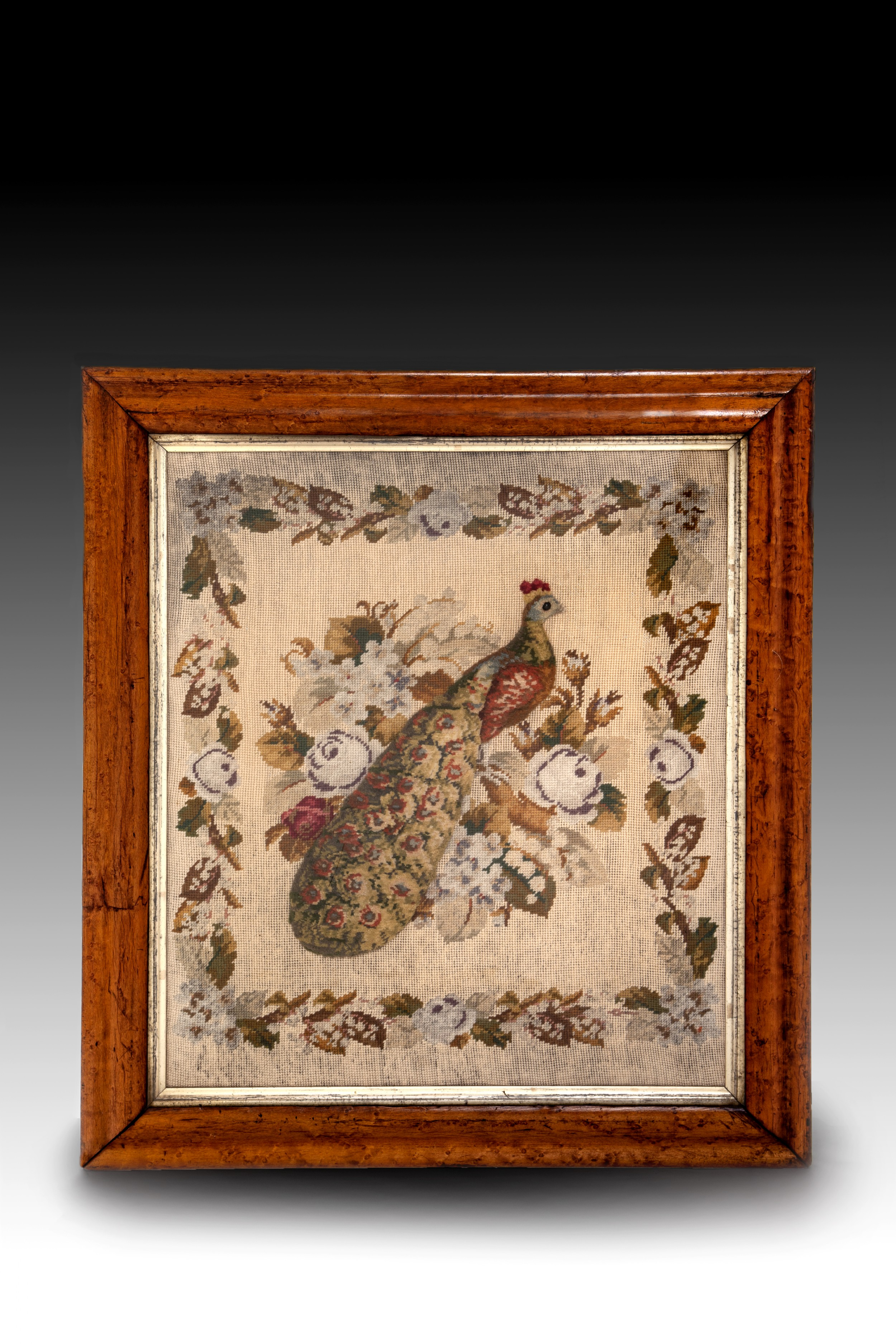 an early 19th century raised turkeywork picture of a peacock in a floral garden setting