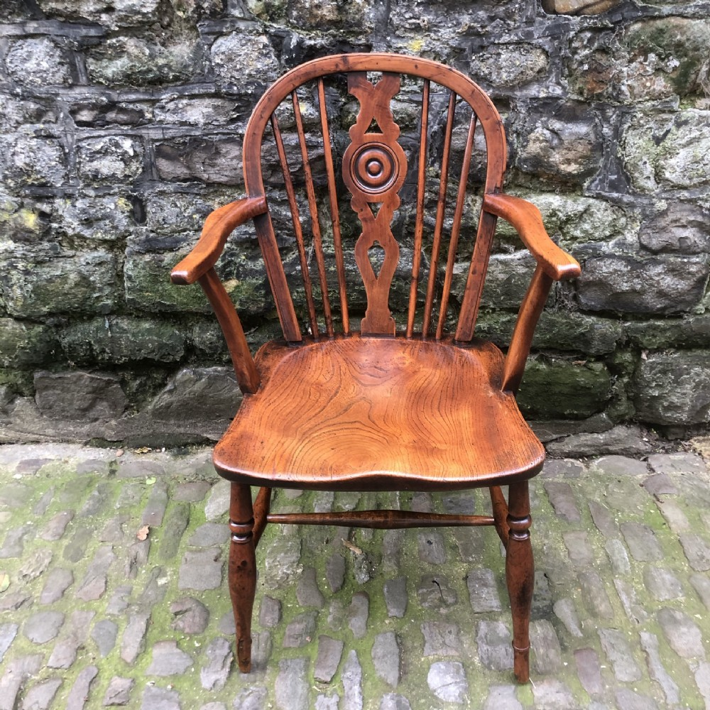 an early 19th century yew and elm draught back windsor chair