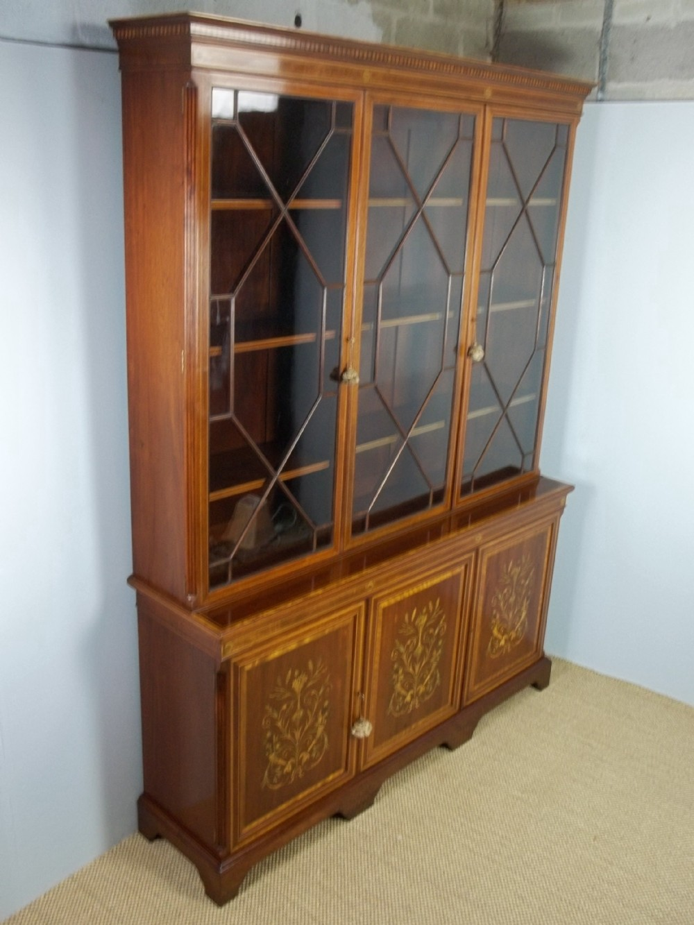 a large antique stamped edwards and roberts mahogany marquetry inlaid triple three door breakfront type bookcase display cabinet with adjustable open bookshelves c1895