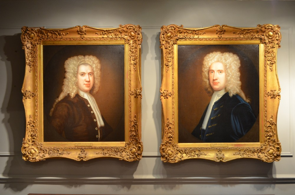 pair of early 18th century oil portrait paintings in original gilt carved frames