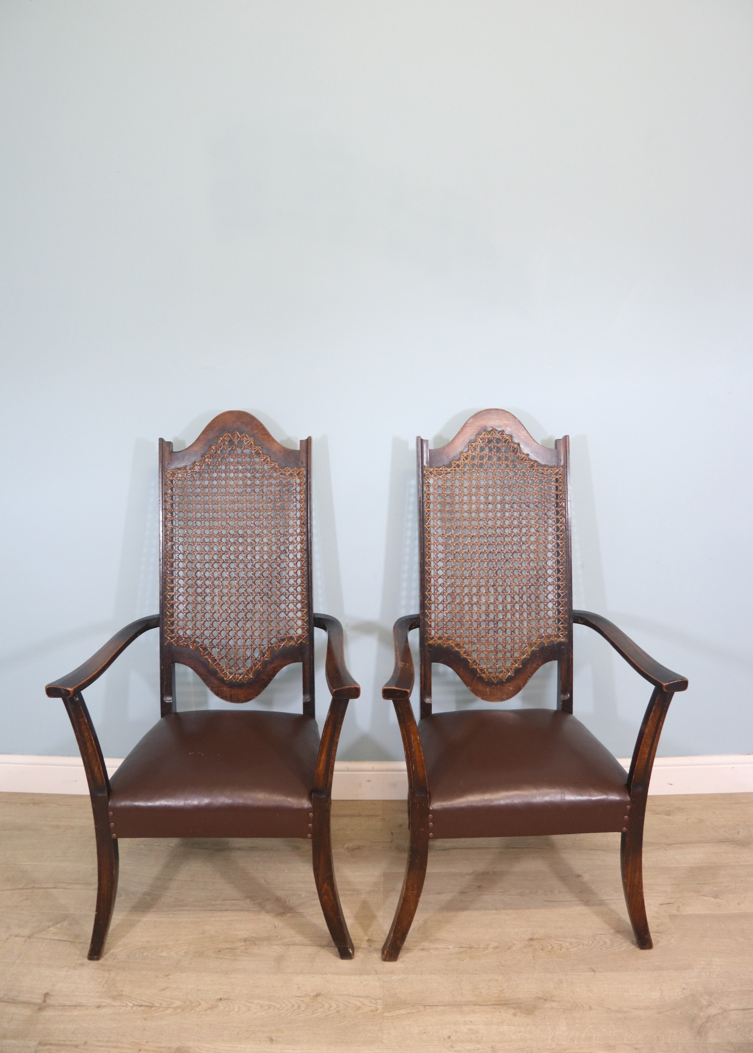 a lovely pair of early 20th century industrial looking cane shield back armchairs