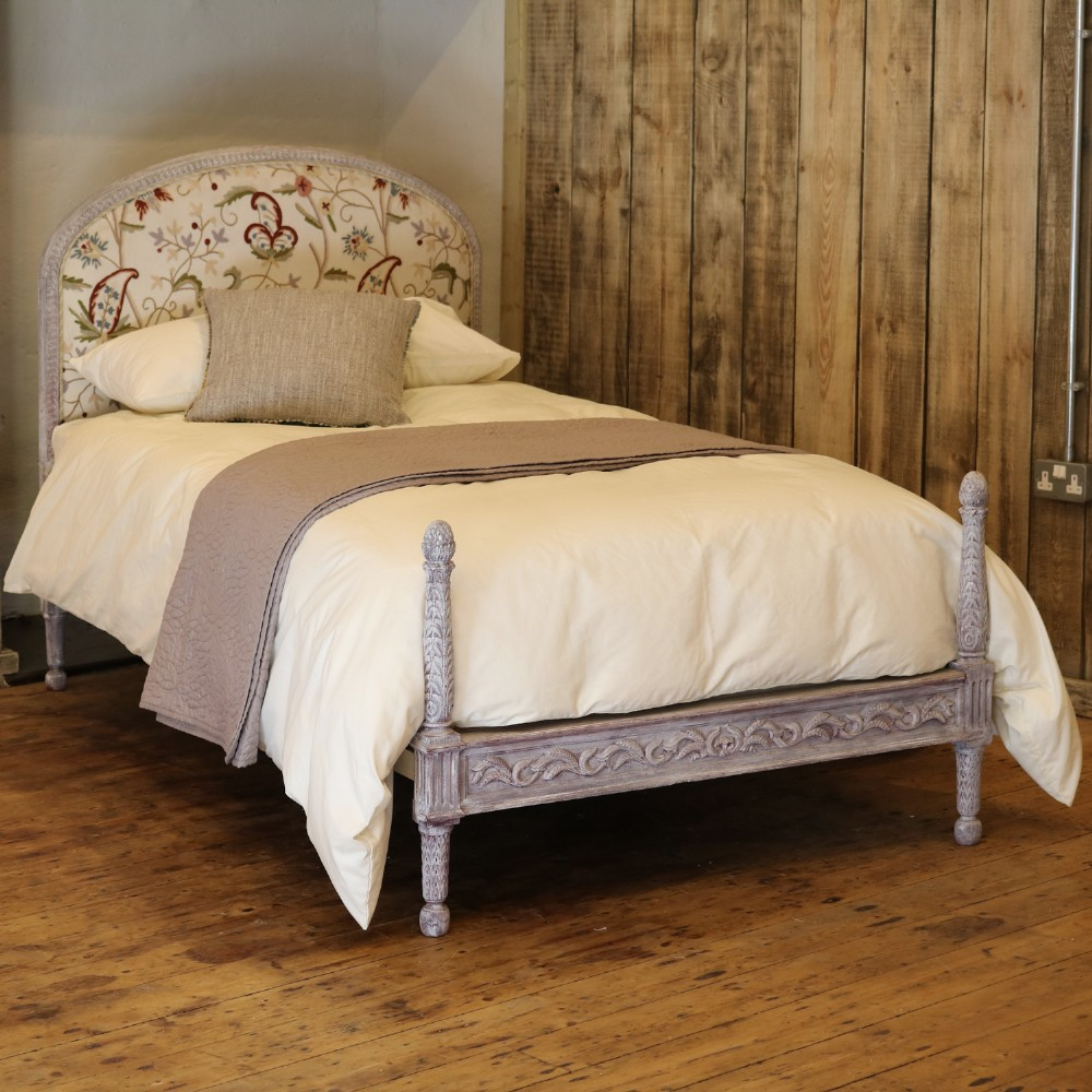 upholstered antique bed with painted frame