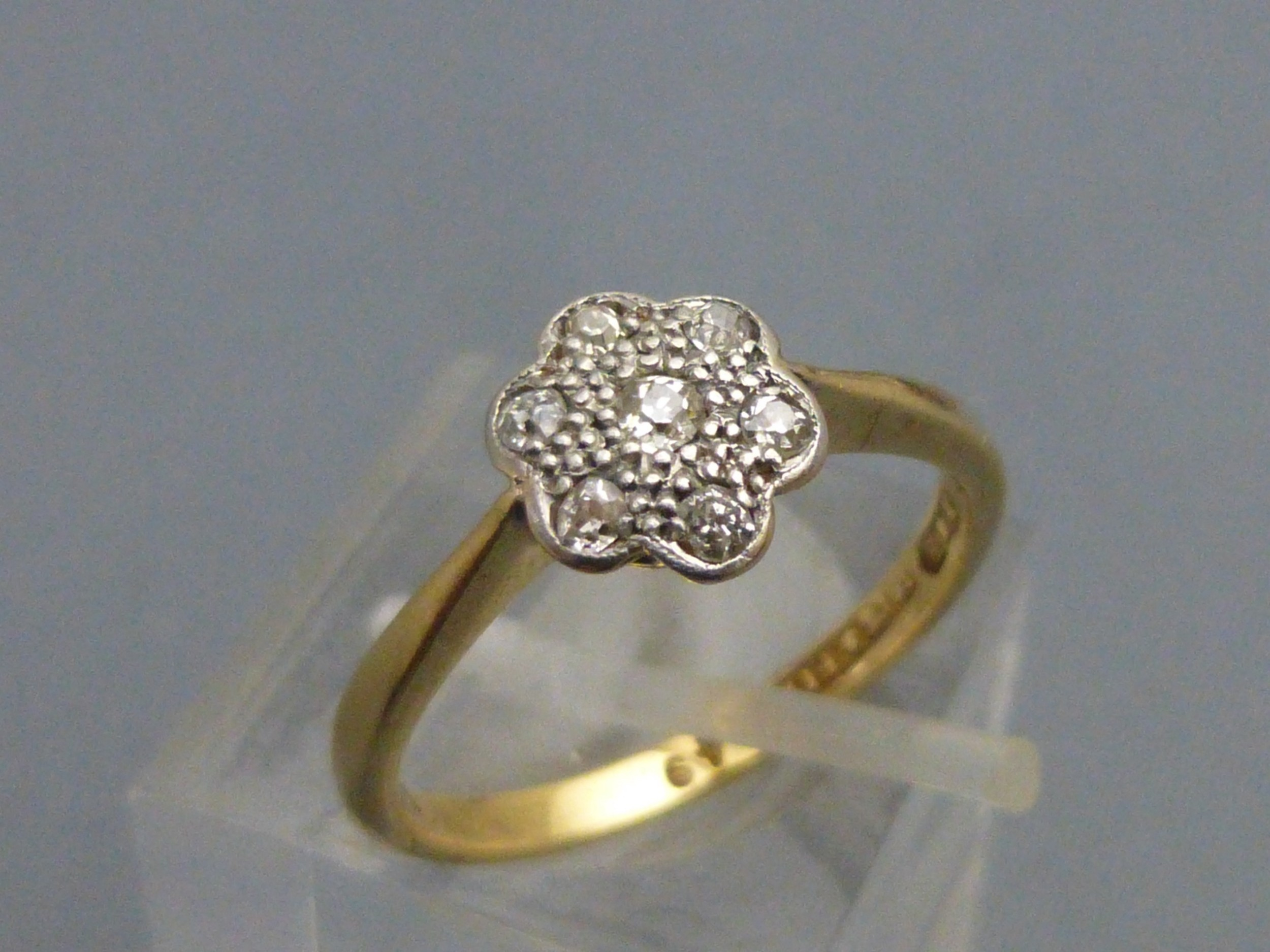an 18ct gold and platinum diamond flower head ring