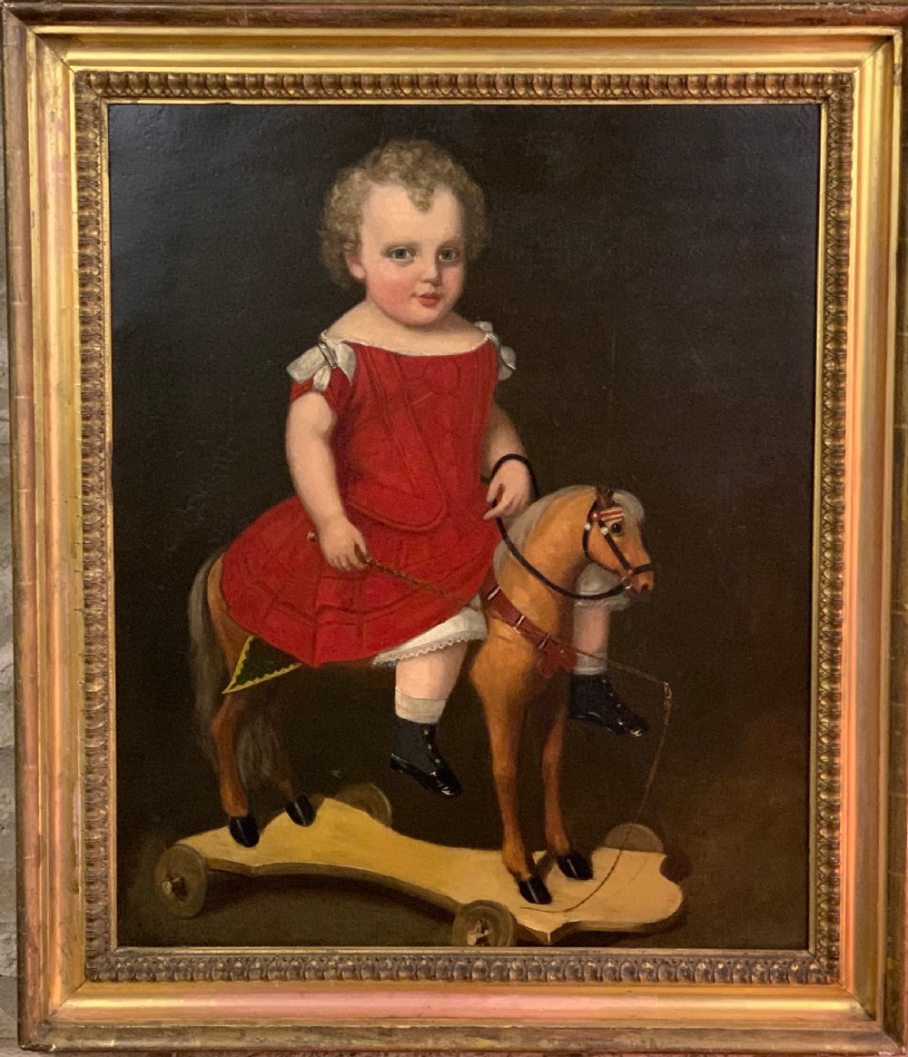 naive c19th c oil of a boy on rocking horse in gilt frame