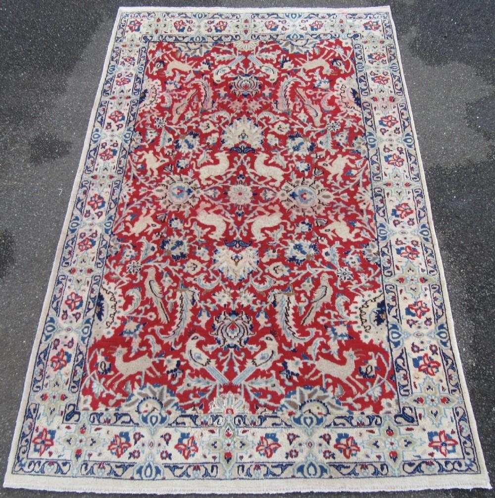 old persian isfahan rug with silk highlights vermillion groundvarious animal bird motifs
