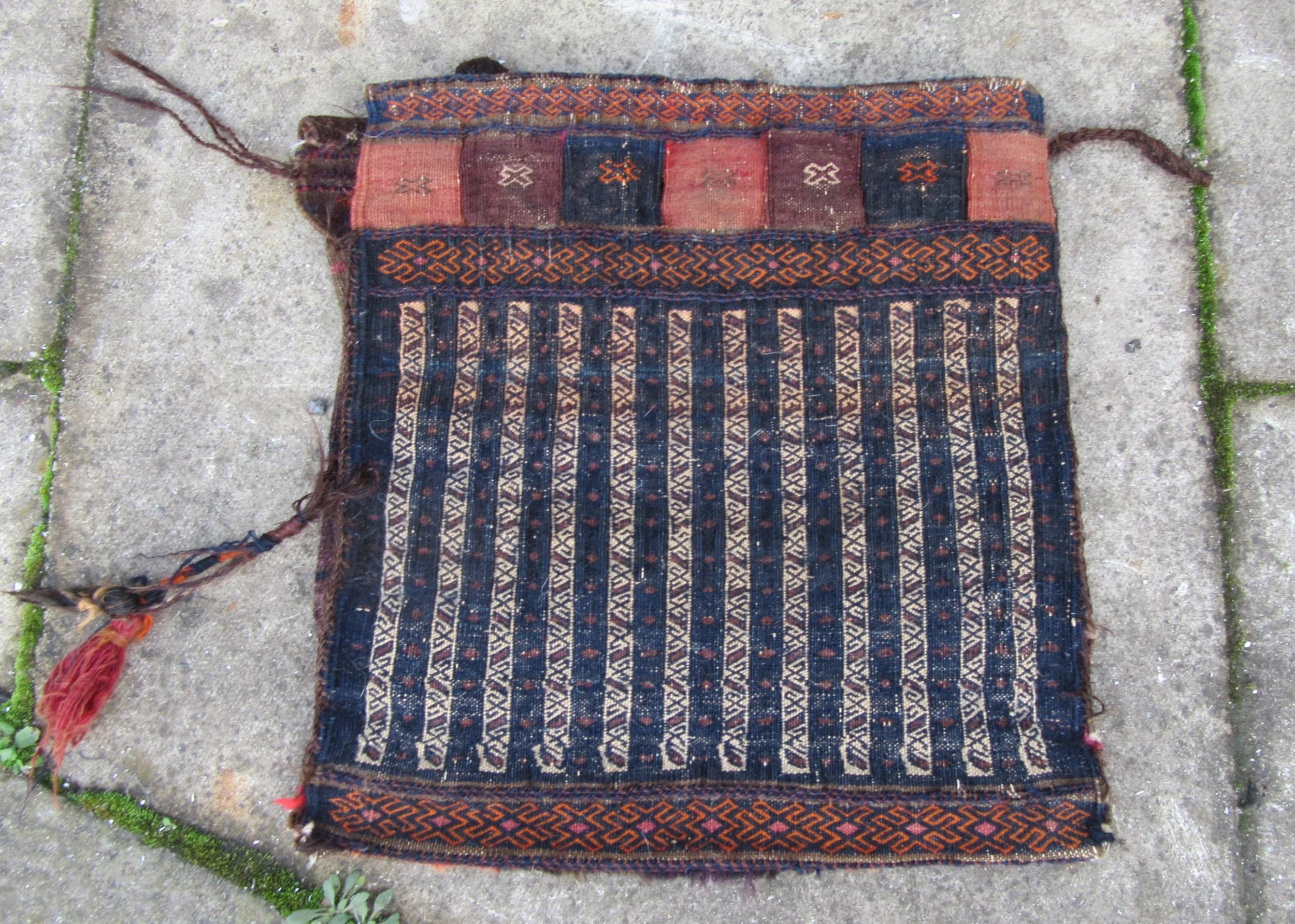 antique baluch saddle bag rug hanging gordon reece gallery label