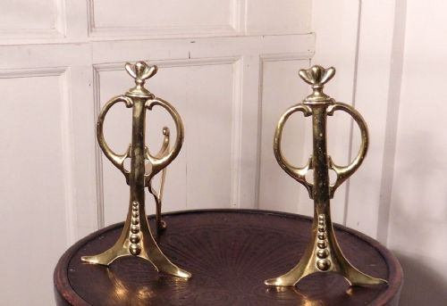 an elegant pair of art nouveau brass andirons or fire dogs