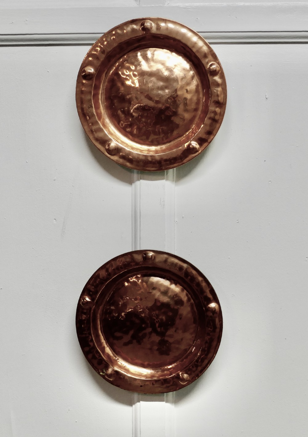 a pair of arts and crafts beaten copper wall plates by lombard