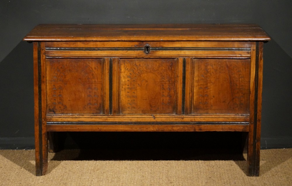 a late 17th century english elm coffer with ebonised decoration and scratched carved panels