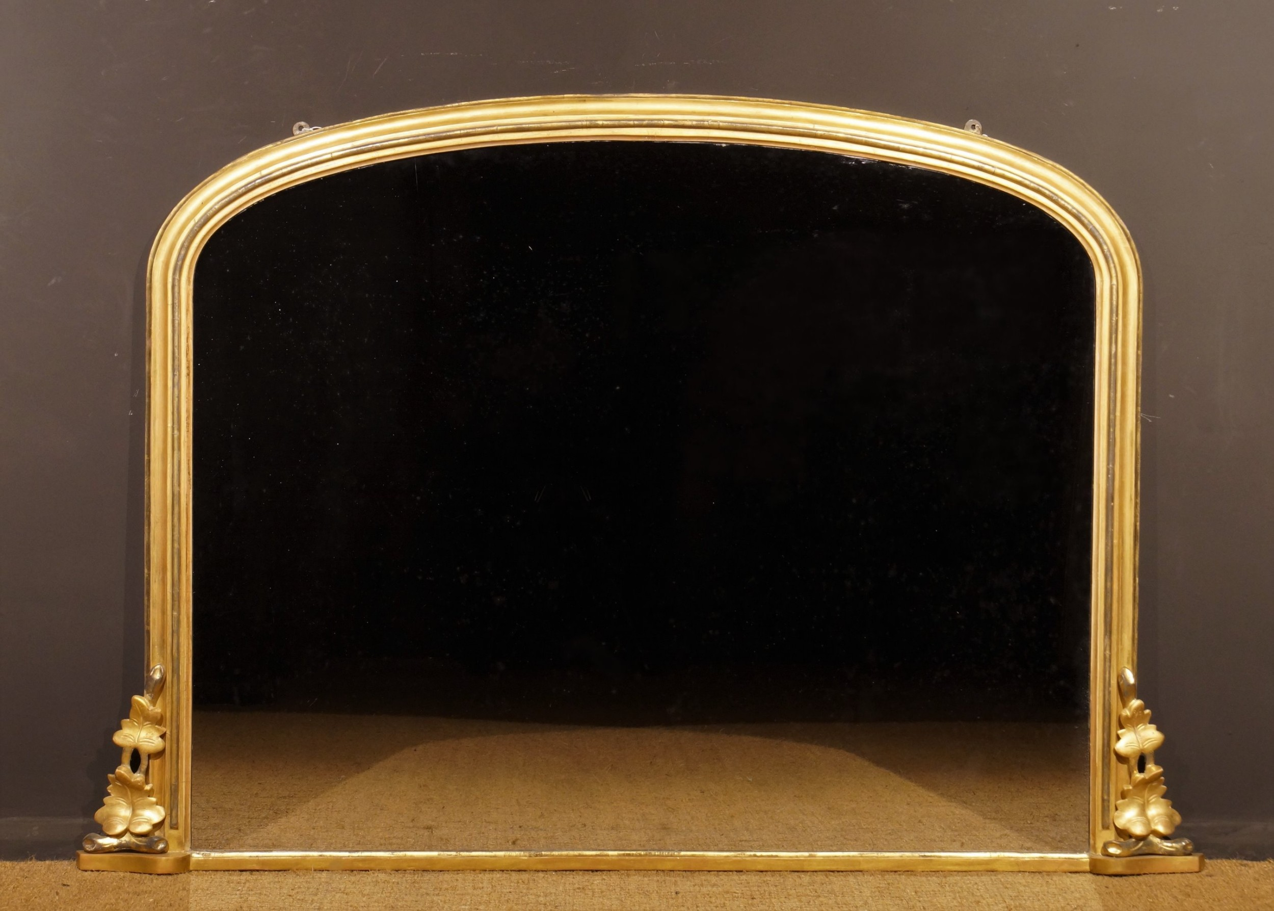 a low 19th century gilded arch top overmantle mirror circa 1840