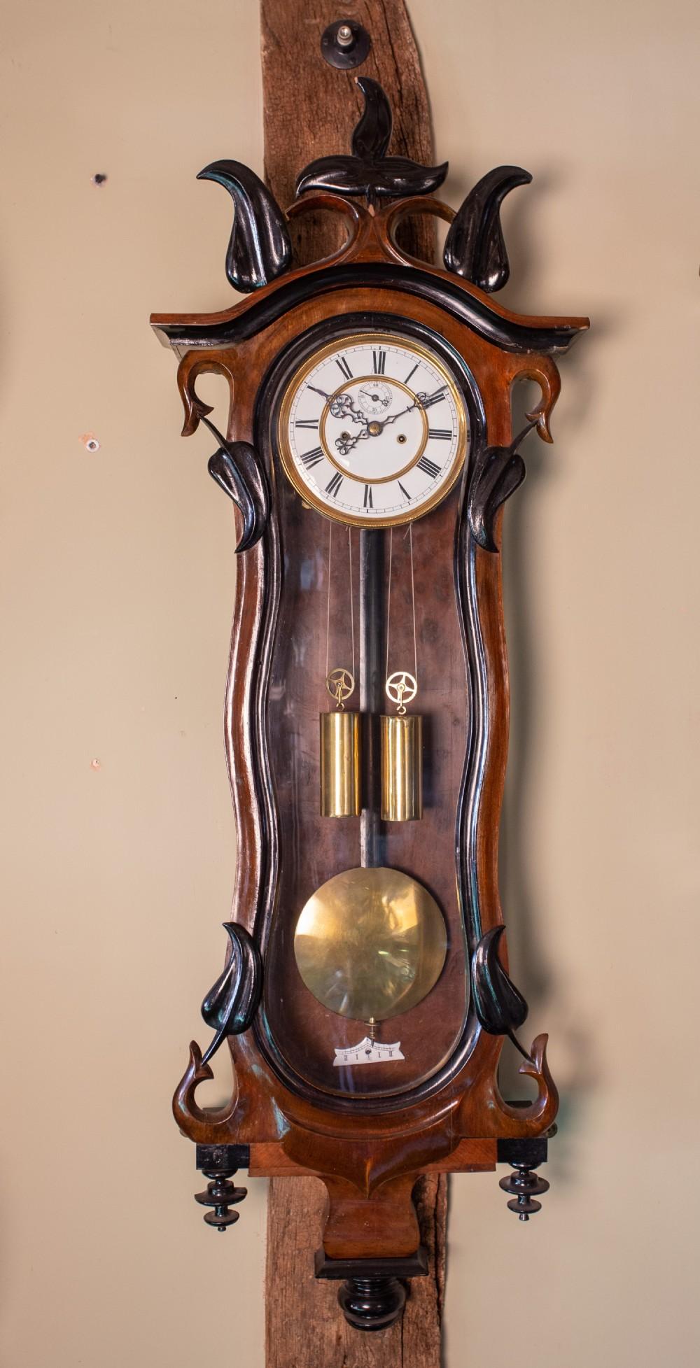 elegant slim vienna regulator in a very organic walnut case in art nouveau style