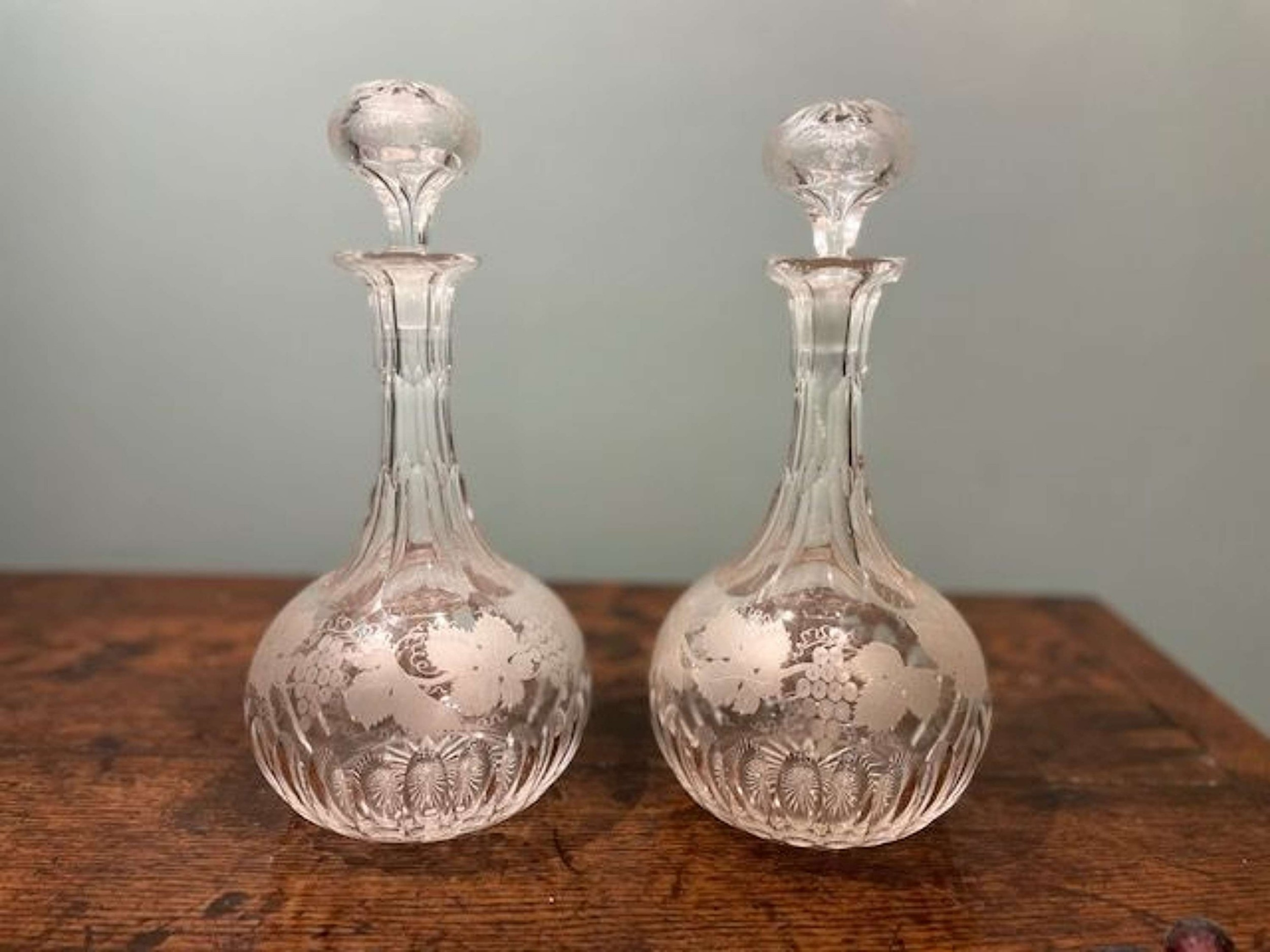 pair of mid 19th c shaft globe decanters with grapevine motifs