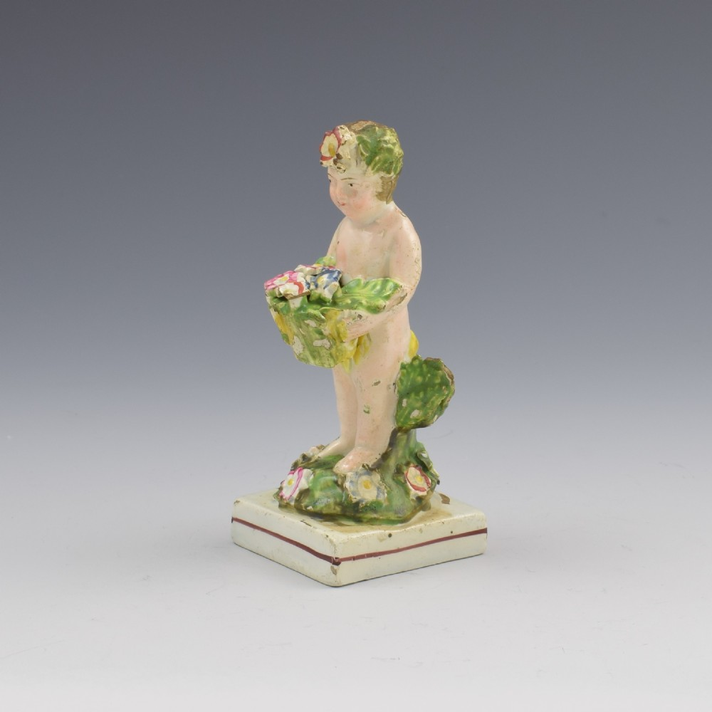 early staffordshire pearlware figure of a putto with basket c1800