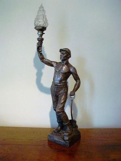 an early 20th century silvered spelter lamp in the form of a miner