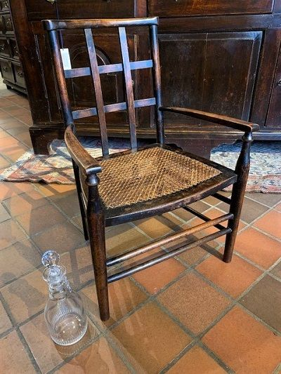 an early 20th beech lattice back child's chair with caned seat attrbuted to liberty co